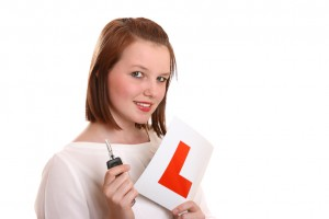 Pretty teenage driver holding L-plates and car key.
